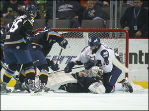 Toledo Walleye goalie Hannu Toivonen (30) is knocked down by Kalamazoo Wings player Brett Ponich (28) in a scrum in front of the net during the first period.