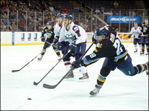 Toledo Walleye player John May (28) fires in a shot against Kalamazoo Wings during the first period.