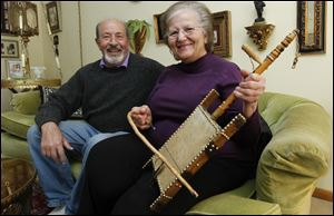 Abraham Sallock sits with Manira Saide-Sallock, holding her father's rababa, a stringed instrument, in their Oregon home. Ms. Saide-Sallock's father, Mohammed, lived in the Little Syria district in the 1940s.