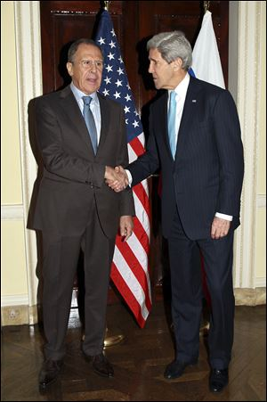 Russian Foreign Minister Sergey Lavrov, left, and U.S. Secretary of State John Kerry shake hands prior to a meeting at Winfield House in London today.
