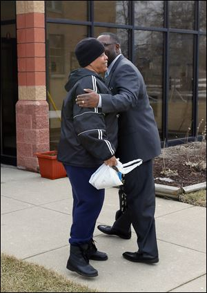 Pastor Arnold, right, greets Sister Lolita McCall while walking in between the church and the New Life Center.