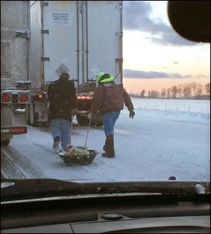 Two men pull a sled containing meals and water to stranded motorists, as seen through the windshield the vehicle of Maureen Dixon of Cleveland. She was stuck for seven hours in the traffic jam caused by the pileup on the Ohio Turnpike on Wednesday.