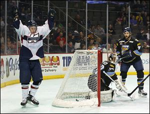 Kalamazoo's Justin Taylor, left, celebrates after scoring a goal on Walleye goalie Hannu Toivonen on Friday.