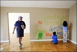 James Bergeron, left, and his children paint good-byes on the wall of their home moments before wreckers demolished it. The project started out as a routine remodel.