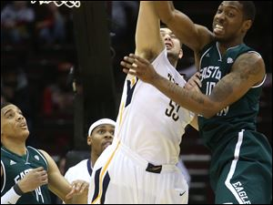 Toledo's Nathan Boothe (53) fights Eastern Michigan's Da'Shonte Riley (10) for a rebound early in the first half.