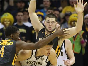 Toledo's Justin Drummond (4) and Nathan Boothe (53) force Western Michigan's Mario Matasovic (31) into turning the ball over on defense in the first half.