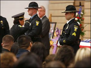 Toledo Police Capt. Diana Ruiz-Krause salutes the coffin.