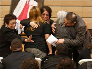 Family members hug before the start of the funeral service.