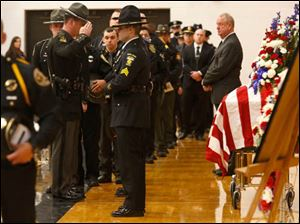 Police officers from around the area salute his coffin during the funeral service of Jose