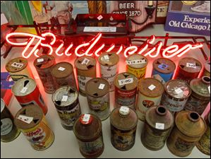 Neon Budweiser signs and cone top beer cans for sale.