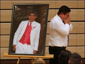 Ramiro Guadalupe Arreola, Andy's cousin,  cries as he walks past the portrait of his cousin Jose