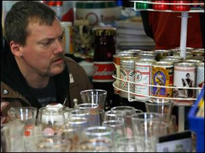 Painsville, Ohio resident Chris Salzer looks at a collection of old and new beer cans.