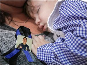 "Emmitt Chavez, 16 months, sleeps near a photo of his father Jose ""Andy"" Chavez, during his father's funeral service at Woodmore High School in Elmore, Ohio."