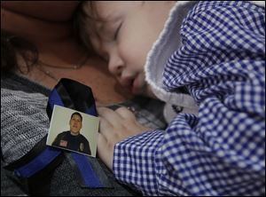 Emmitt Chavez, 16 months, sleeps near a photo of his father, Jose 'Andy' Chavez, during the funeral service.