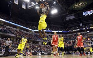 Michigan guard Caris LeVert dunks in the first half.