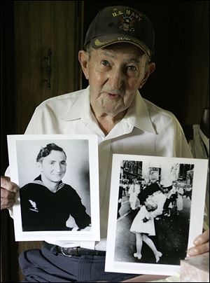 Glenn McDuffie holds a portrait of himself as a young man, left, and a copy of Alfred Eisenstaedt's iconic Life magazine shot of a sailor embracing a nurse in a white uniform, right, at his Houston home in this 2007 file photo.