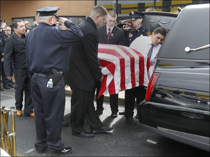 CTY funeral16p Police salute as family members place the coffin of Jose 'Andy' Chavez into the hearse at Woodmore High School. Scores of law enforcement workers and firefighters attended the rite.