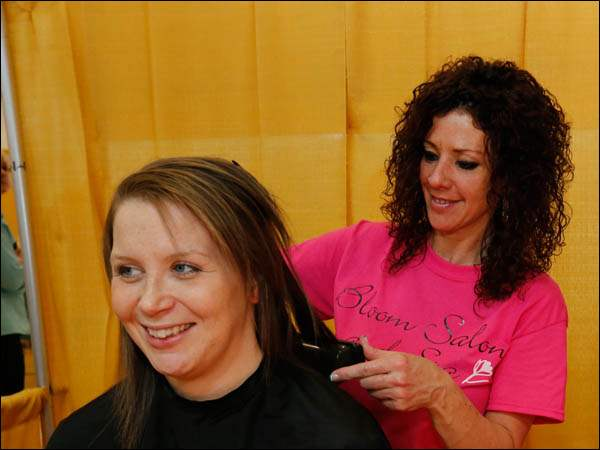 Katie Rosenberger of Toledo, left, receives a free haircut from Cristey Sparks of Temperance and from Bloom Salon and Spa, a Temperance, Mich., business.