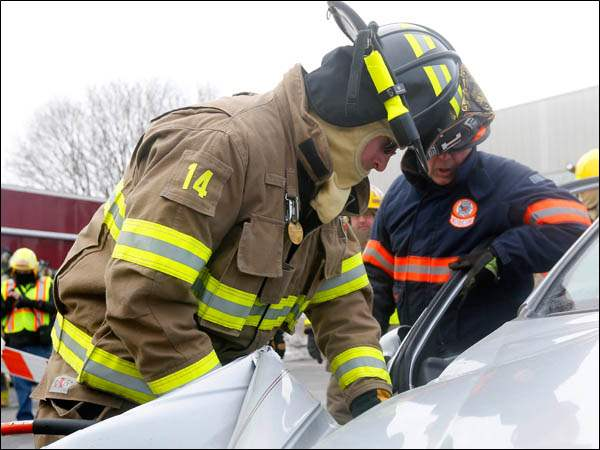 "Peter Fiset, right, Regional Manager with Holmatro and a trainer with the Northwestern Ohio Volunteer Firemen's Association, observes the performance of firefighter Jason Gillfillan, left,  while he uses the ""jaws of life""  to perform a practice rescue."