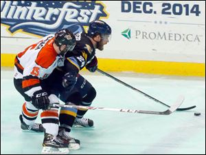 The Walleye's Jesse Messier and the Komets' Mike Embach chase the puck.