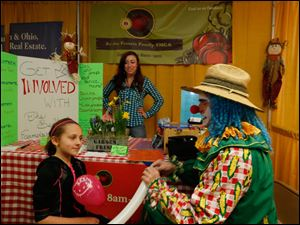 Abby Miller, 10, of Temperance, Mich., left, gets a balloon headdress from Happy the Clown at the Bedford Farmer's Market table at the trade fair. Staffing the table is Alie Miller of Lambertville, Mich. Happy the Clown is Matt Onweller of Swanton.