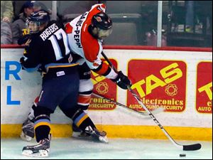 Toledo's Kyle Rogers tries to keep the Komets' Simon Danis-Pepin from getting control of the puck.