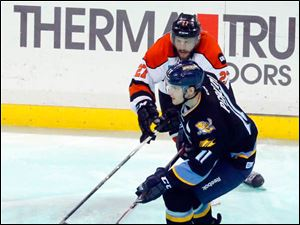 The Walleye's Brett Perlini, left, and the Komets'  Shawn Szydiowski fight for the puck.