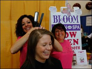 Cristey Sparks of Bloom Salon and Spa, a Temperance, Mich., business, gives a free haircut to Katie Rosenberger of Toledo.
