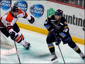 The Walleye's J.P. Burkemper takes the puck around the goal with the Komets' Nathan Martine in pursuit.