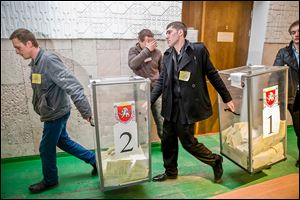Referendum officials move boxes of paper ballots at a polling station after voting ended in Simferopol, Ukraine. The Crimeans' vote, unrecognized both by the Ukrainian government and the West, was Sunday.