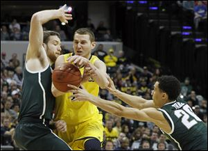 Michigan State's Matt Costello, left, and Travis Trice pressure Michigan's Nik Stauskas into losing control of the ball. Despite his struggles, Stauskas led the Wolverines with 17 points.