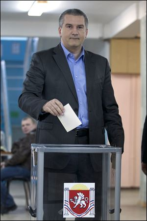 The head of Crimea's unrecognised Russian-backed government Sergei Aksyonov goes to cast his ballot at a polling station Sunday in Simferopol, Ukraine.