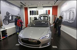 Customers check out a new Tesla all electric car, today, at a Tesla showroom inside the Kenwood Towne Centre in Cincinnati.