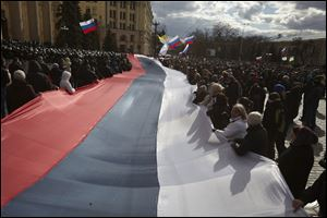 Pro-Russia demonstrators chant slogans as they carry a giant flag during a rally at a central square in Kharkiv, Ukraine, to show their support for the Crimean referendum Sunday.