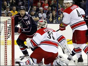 Carolina Hurricanes goalie Anton Khudobin (31), of Kazakhstan, and Andrej Sekera (4), of Slovakia, watch Columbus Blue Jackets' R.J. Umberger's shot go past the net.