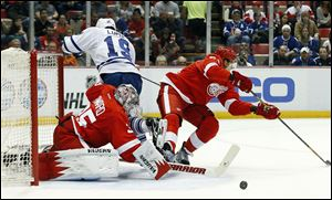 Detroit Red Wings goalie Jimmy Howard (35) stops a Toronto Maple Leafs right wing Joffrey Lupul (19) shot as defenseman Danny DeKeyser defends.