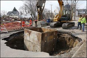 Construction workers excavate a sinkhole that opened up Tuesday on Fernwood Avenue near its intersection with North Detroit Avenue in Toledo. The hole was originally about 10 feet wide, but crews enlarged it in an effort to determine what caused the sink-hole. When they were done, the hole measured about seven feet deep and about 15 feet wide.