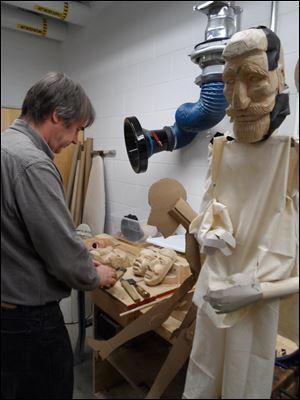 Bradford Clark works on the faces of  townspeople puppets for 'Frankenstein.' At right is the Victor Frankenstein puppet in a preliminary stage.