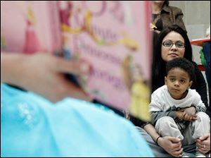 Ana Rodriguez and her son Xavier Rodriguez, 4, from Toledo, listen as Laurel Lovitt, who is in character for her business