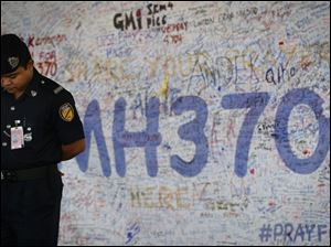 Malaysia airport police officer stands in front of  messages board for the passengers aboard a missing Malaysia Airlines plane at Kuala Lumpur International Airport in Sepang, Malaysia, today.