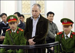 Dissident blogger Pham Viet Dao, standing at center,  appears at a court in Hanoi, Vietnam today.