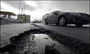 A car drives by a pothole in Detroit.