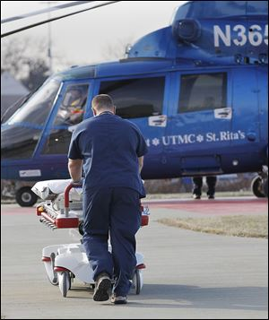 A paramedic wheels a bed to a Life Flight helicopter to transport a vehicular accident victim to the University of Toledo Medical Center.