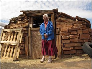 Navajo elder Stella Peshlakai Smith, 89, stands outside a traditional dwelling on her homestead at Wupatki National Monument in northern Arizona.