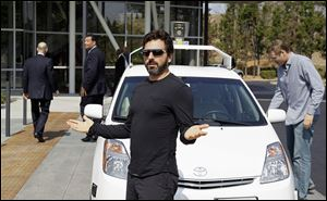 Google co-founder Sergey Brin gestures after riding in a driverless car in 2012 at Google headquarters. While most investors aren't worried about the experiments, experts point out that Google X has yet to produce a major economic hit.