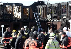 Firefighters investigate an early morning fire at the Mariner's Cove Hotel in Point Pleasant Beach, N.J. today. At least three people were killed at the hotel whose residents included Superstorm Sandy victims whose homes were destroyed in the hurricane.