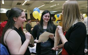 University of Toledo fourth-year medical students Pamela Glennon, Madeline Heald, and Alexandra Paraskos, from left, show each other their letters during the annual Residency Match reception at the Stranahan Theater's Great Hall in South Toledo.