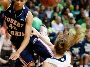 RMU's Kelly Hartwell (42) and Notre Dame's Janee Brown (11), collide in the first period.