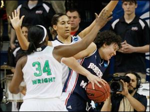 RMU's Artemis Spanou (15) spins out from between Notre Dame defenders Markisha Wright (34) and Taya Reimer (12).