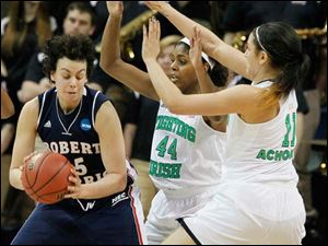 RMU's Artemis Spanou is double teamed by UND's Ariel Braker (44) and Natalie Achonwa (11), in the second period.